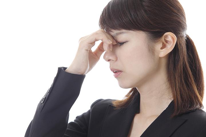 眉間を押さえた女性のイメージ